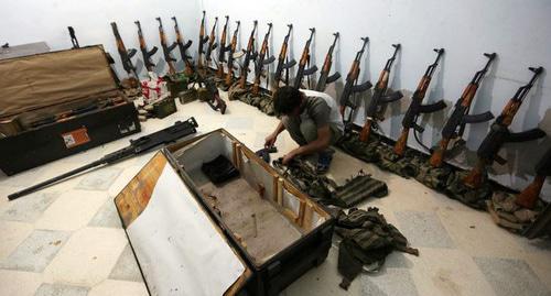 Боевик 'Аль-Султан Мурад бригады' на складе оружия  на севере Сирии. Фото Khalil Ashawi/ REUTERS