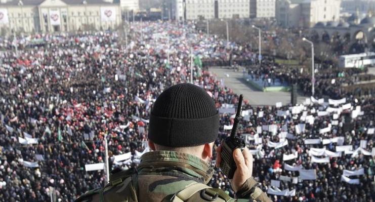 Силовик наблюдает за скоплением людей на площади в Грозном. Фото: REUTERS/Eduard Korniyenko