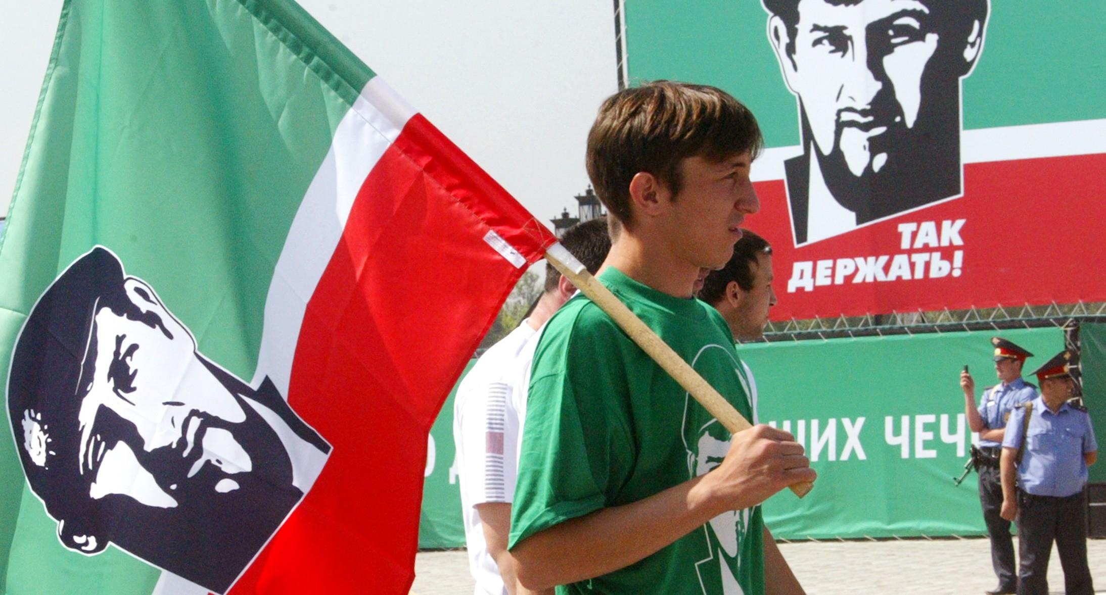 Молодой человек в Грозном с флагом с портретом Кадырова. REUTERS/Said Tsarnayev