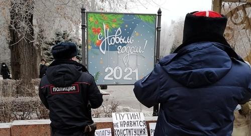 """Полицейский и казак записали данные пикетчиков и сфотографировали их плакаты. Волгоград, 31 декабря 2020 года. Фото Татьяны Филимоновой для """"Кавказского узла""""."""
